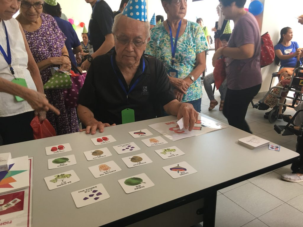 A photo of elderly having fun with our memory matching game at Monfort Care Goodlife 16th anniversary event. It was held at Blk 15A Marine Terrace.